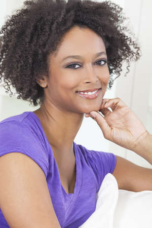 settee: A beautiful mixed race African American girl or young woman looking happy and thoughtful