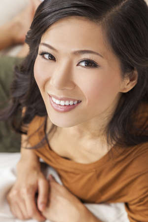 A beautiful young Chinese Asian Oriental woman with a wonderful toothy smile  photo