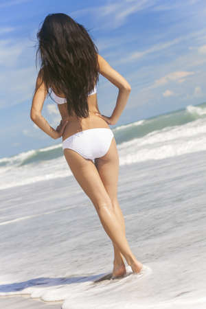 Rear view of a sexy young brunette woman or girl wearing a white bikini standing in the surf on a deserted tropical beach with a blue sky  photo