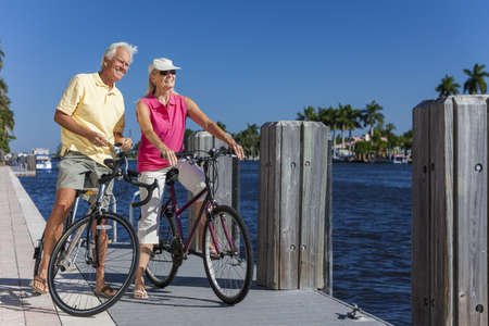 Happy senior man and woman couple together cycling on bicycles with bright clear blue sky by a river or sea photo