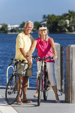 Happy senior man and woman couple together cycling on bicycles with bright clear blue sky by a river or sea