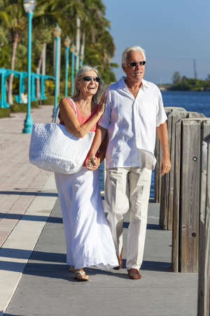 Happy senior man and woman romantic couple walking together, holding hands & looking out to tropical sea or river with bright clear blue sky photo