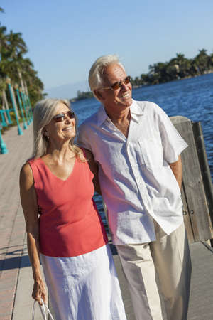 Happy senior man and woman romantic couple together looking out to tropical sea or river with bright clear blue sky photo