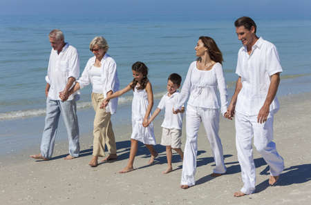generations: A happy family of grandparents, mother, father and two children, son and daughter, walking holding hands and having fun in the sand of a sunny beach Stock Photo