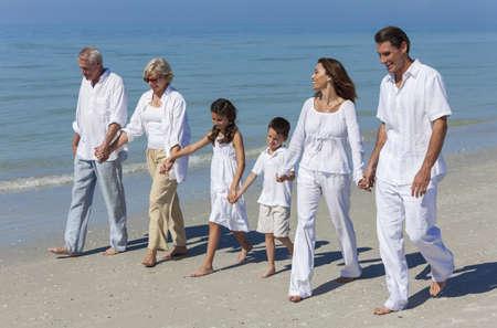 Een gelukkige familie van grootouders, moeder, vader en twee kinderen, zoon en dochter, wandelen bedrijf handen en plezier in het zand van een zonnig strand