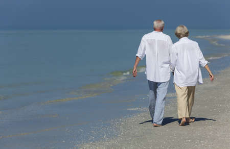 Rear view of happy senior man and woman couple walking and holding hands on a deserted tropical beach with bright clear blue sky