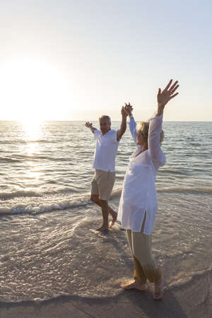 aging woman: Happy senior man and woman couple walking and holding hands on a deserted tropical beach with bright clear blue sky Stock Photo