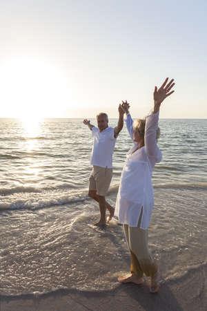 tercera edad: Hombre feliz senior y par mujer que camina y tomados de la mano en una playa desierta tropical con brillante cielo azul claro