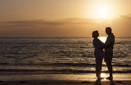 Happy senior man and woman couple together hugging embracing at sunset on a deserted tropical beach
