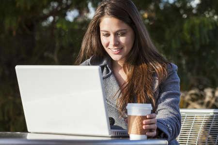 Una mujer joven o joven estudiante con una computadora port�til fuera y beber caf� para llevar Foto de archivo