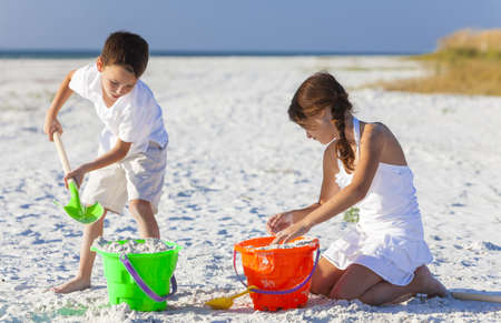 Happy children, boy & girl, brother& sister having fun playing in the sand on a beach with bucket and spade Stockfoto