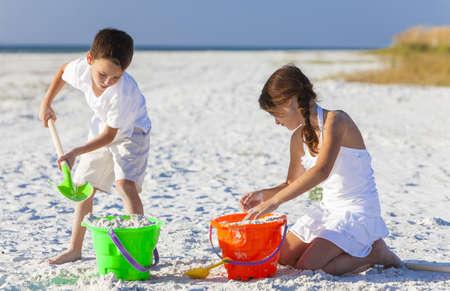 Ni�os felices, chico y chica, hermano y hermana que se divierten jugando en la arena en una playa con el cubo y la pala