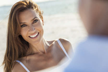 Beautiful smiling middle aged woman with man couple together in sunshine on a beautiful tropical beach photo