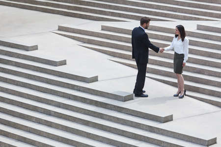 A caucasian man businessman and an Asian woman businesswoman shaking hands on a deal standing on modern city steps photo