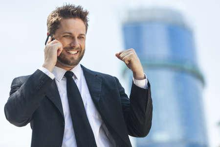 Un hombre joven y exitoso, hombre de negocios ejecutivo masculina hablando por su tel�fono celular m�vil celebrando en frente de un edificio de oficinas de gran altura en una ciudad moderna