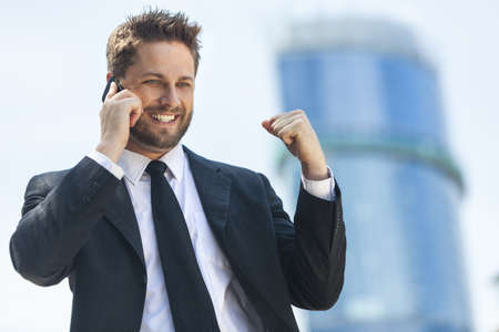 A young successful man, male executive businessman talking on his mobile cell phone celebrating in front of a high rise office block in a modern city