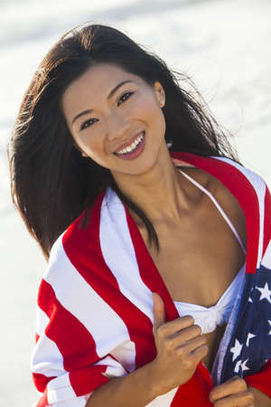 chinese american: Beautiful young Chinese Asian woman laughing wearing bikini and wrapped in American flag towel on a sunny beach