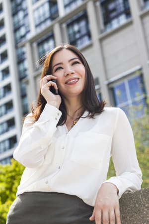 businessowman: Portrait of a smiling happy young Asian woman or businessowman talking on her cell phone