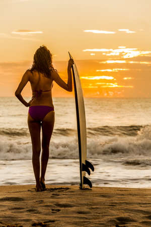 Solarised style photograph rear view of beautiful sexy young woman surfer girl in bikini with white surfboard on a beach at sunset or sunrise