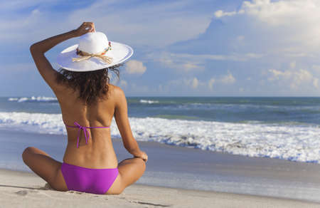 A sexy young brunette woman or girl wearing a bikini and sun hat sitting on a deserted tropical beach with a blue sky  photo