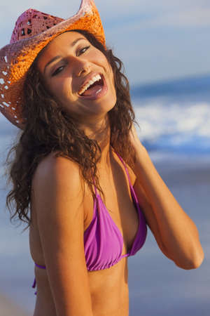 Beautiful smiling laughing happy young mixed race sexy Hispanic woman in bikini and cowboy hat on a tropical beach