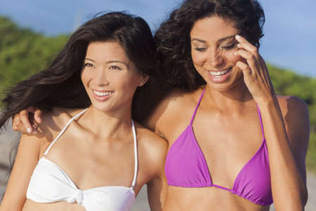 Two beautiful young women one Chinese Asian the other mixed race Hispanic in bikinis having fun at the beach photo