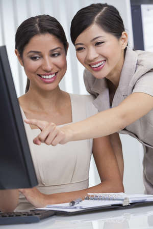 Portrait of beautiful young mixed race Hispanic woman or businesswoman in office meeting with Chinese Asian female colleague using a desktop computer monitor photo