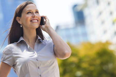 businessowman: Portrait of a smiling happy young woman or businessowman talking on her cell phone Stock Photo
