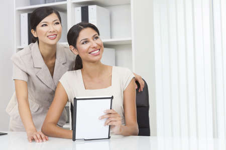 Portrait of beautiful young mixed race Hispanic woman or businesswoman in office meeting with Chinese Asian female colleague using a tablet computer  photo