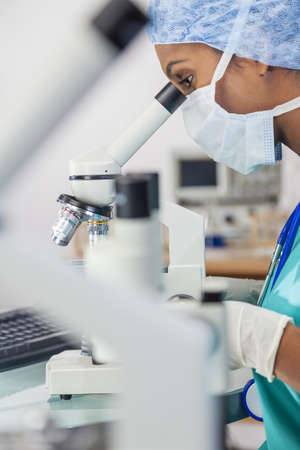 An Asian female medical doctor or scientific researcher using her microscope in a laboratory  photo