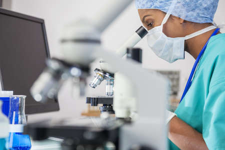 An Asian female medical doctor or scientific researcher using her microscope in a laboratory