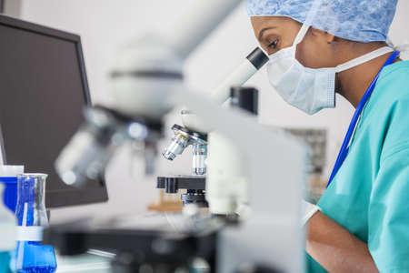 investigador cientifico: Un asi�tico m�dico femenino o investigador cient�fico utilizando su microscopio en un laboratorio