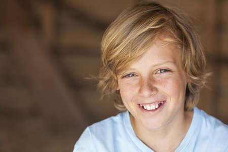 Young happy smiling blond boy child aged about 12 or early teenager
