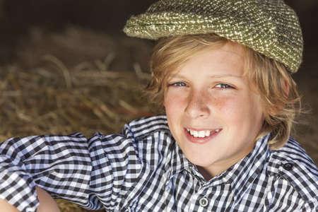 chemise carreaux: Heureux le jeune enfant gar�on blond sourire adolescent �g� d'environ 12 ou au d�but v�tu d'une chemise � carreaux et casquette plate assis sur le foin ou de paille Banque d'images