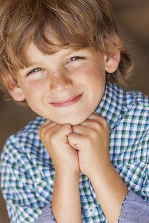 chemise carreaux: Heureux le jeune enfant gar�on blond souriant portait chemise � carreaux reposant sur ses mains