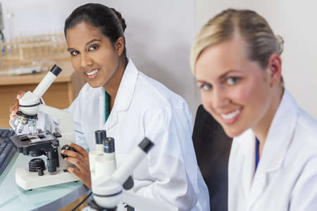 An Indian Asian female medical or scientific researcher or doctor using her microscope in a laboratory with her colleague.
