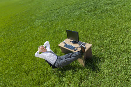 businessman relaxing feet up at a desk with a computer in a green field  photo