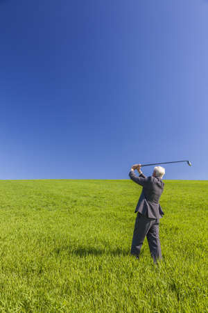 an old male man businessman playing golf in a green field with a blue sky  photo