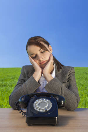 businessowman: Business concept shot of a beautiful young woman businessowman sitting at a desk waiting for old vintage telephone to call in  green field with a bright blue sky