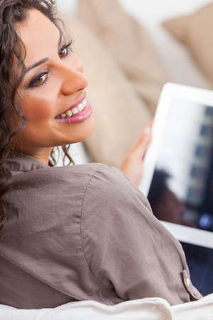 Beautiful young Latina Hispanic woman laughing, relaxing and using a tablet computer photo