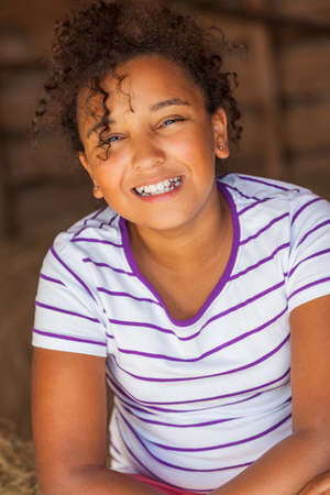 cheeky: A beautiful and happy mixed race African American female girl child smiling sitting in hay filled barn