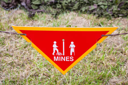 Land mine or minefield danger warning sign in a war zone area