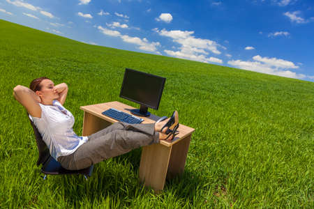Business concept beautiful woman sitting relaxing day dreaming at desk feet up with computer in a green field with bright blue sky & fluffy white clouds.