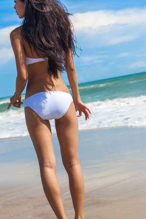 bikini sexy: Rear view of a sexy young brunette woman or girl wearing a white bikini on a deserted tropical beach with a blue sky