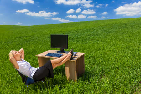 Business concept shot of a beautiful young woman businesswoman relaxing with her feet up at a desk with a computer in a green field with a bright blue sky photo