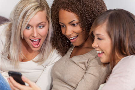 Interracial group of three beautiful young women girl friends at home sitting together on a sofa smiling, surprised and shocked using cell phone smartphone Standard-Bild