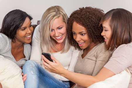 Interraciale groep van drie mooie jonge vrouwen meisje vrienden thuis zitten samen op een bank glimlachen, verbaasd en geschokt met behulp van mobiele telefoon smartphone
