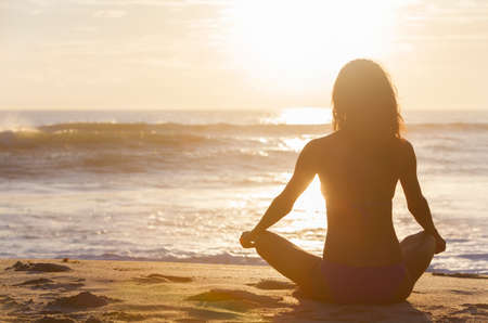 yoga girl: A relaxed sexy young brunette woman or girl wearing a bikini sitting on a deserted tropical beach at sunset or sunrise Stock Photo