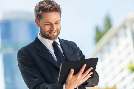 business men: A smart young businessman with a beard using a tablet computer