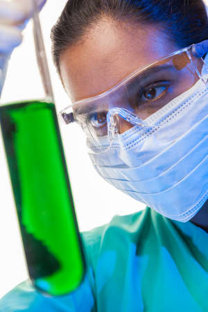 Asian Indian female medical or scientific researcher or doctor looking at a green solution in a laboratory  photo